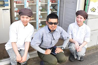 吉野農園の吉野崇弘さんとうーおスタッフ 直売所の前で
